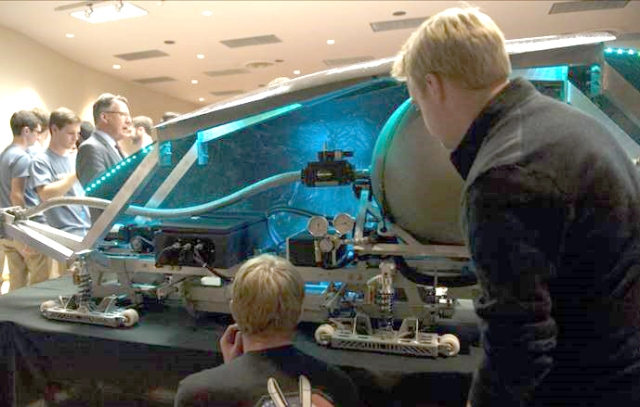 Attendees examine the pod
